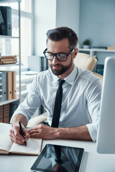 Elegant young man in formalwear writing something in note pad while sitting in the office